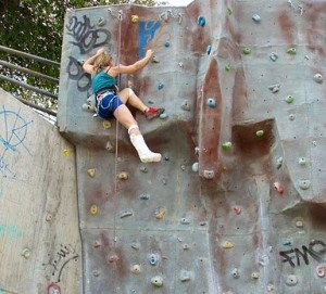 Isabel climbing a rock wall with a leg cast.